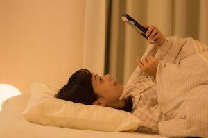 夜遅くまでスマホを触る女性